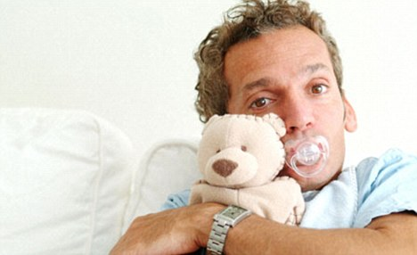 A man sucking a pacifier, wearing a bib, and holding a teddy bear
