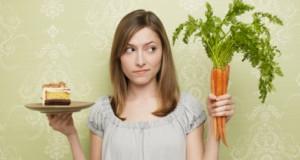 Woman choosing between cake and carrots