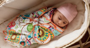A baby in a swaddle blanket