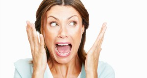 Closeup of shocked woman over white background