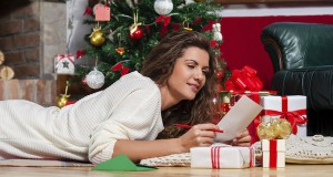 Woman lying on carpet  writing a christmas card